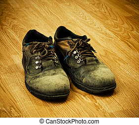trekking boots - pair of old used trekking boots on the wood...