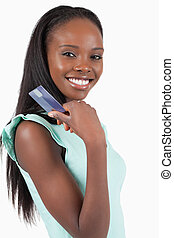 Smiling young woman with her credit card against a white...