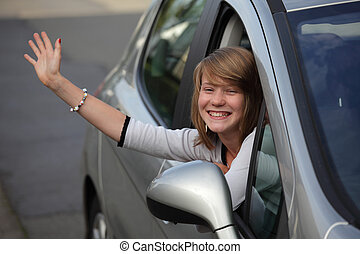 Girl waving goodbye from car - Thirteen year old teenage...