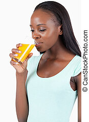 Side view of young woman drinking orange juice