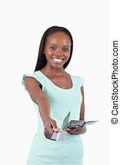 Smiling young woman paying with her credit card against a...