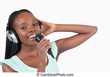 Woman with headphones on singing