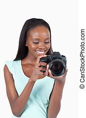 Young photographer taking a look at her cam against a white...