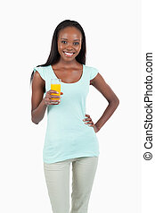 Smiling young woman with a glass of orange juice