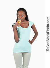 Smiling young woman enjoying a sip of orange juice