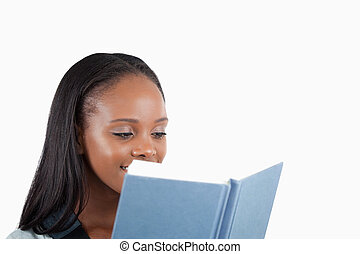 Side view of young woman reading a book against a white...