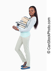 Side view of young woman carrying a stack of books against a...