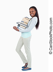 Side view of smiling woman carrying a stack of books against...