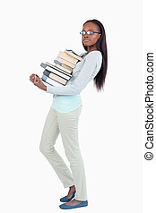 Side view of young woman carrying a pile of books against a...
