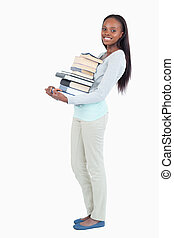 Side view of smiling young woman carrying a stack of books...