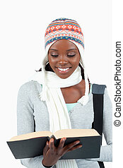 Close up of smiling student in winter clothes reading in her...