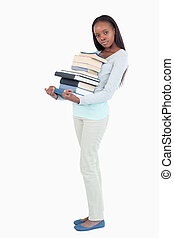 Side view of young woman with a pile of books against a...