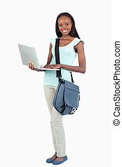 Side view of female student with her laptop against a white...