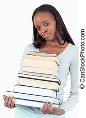 Sad smiling woman with pile of books against a white...