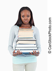 Sad looking young woman with stack of books against a white...