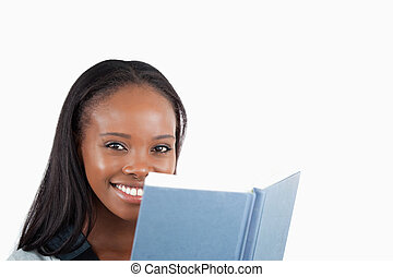 Side view of smiling woman reading a book against a white...