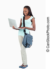 Side view of young student with her laptop against a white...