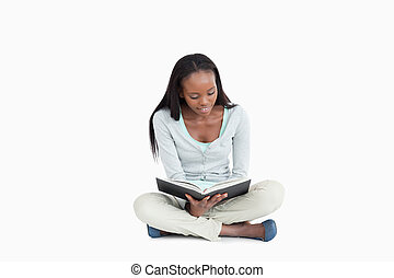 Young woman sitting cross-legged on the floor reading...