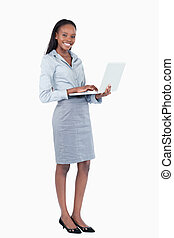 Portrait of a happy businesswoman using a laptop while...