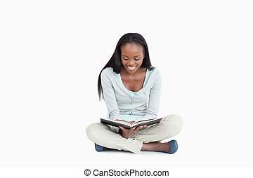 Young woman sitting on the floor reading a book