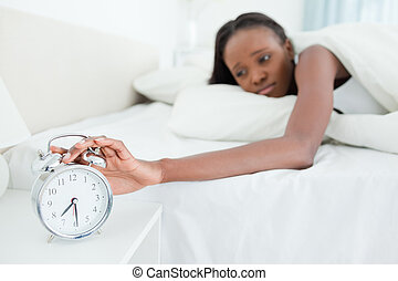Woman switching off her alarm clock in her bedroom