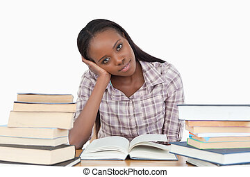 Young woman sitting on her desk with piles of books