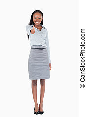 Portrait of a businesswoman with her thumb up against a...
