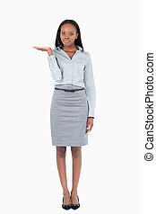 Portrait of a businesswoman presenting something against a...