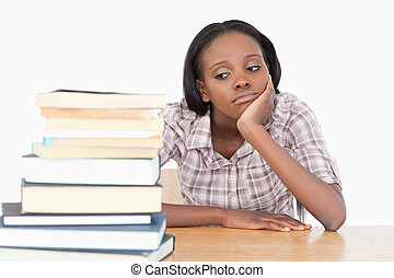 Bored student looking at a stack of books against a white...