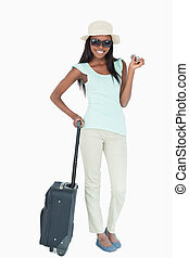 Smiling young woman going on vacation against a white...