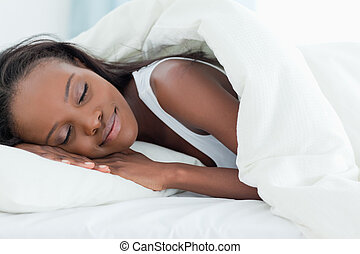 Happy woman sleeping in her bedroom