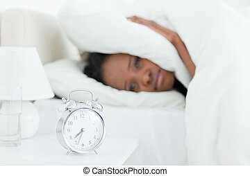 Young woman covering her ears while her alarm clock is ringing