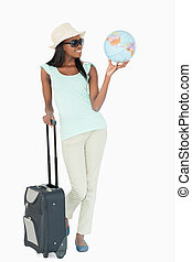 Smiling young woman traveling the world against a white...