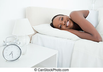 Woman waking up with her alarm clock