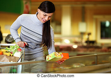 In supermarket - Image of pretty woman with cart choosing...