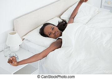 Woman stretching her arms while waking up in her bedroom