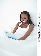 Portrait of a happy woman reading a book