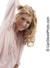 blond young girl with curly hair smiling with attractive pose