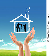 human hands holding model of a house nature background -...