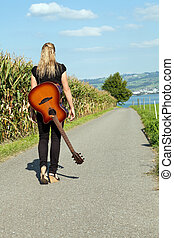 Guitarist walking down country road - Photo of a female...