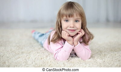 Girl lying on the carpet smiles