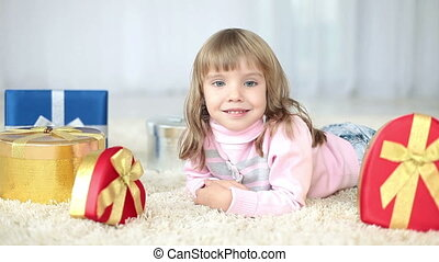 Girl with gifts lying on the carpet