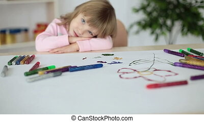 Girl lying on a table looking at ca - Childhood
