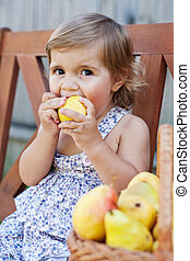 little girl with appetite is a juicy pear