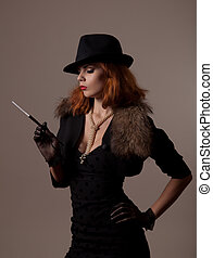 Gangster woman in fedora hat and evening dress holding...