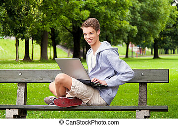 teenager with laptop outdoors - a teenager with laptop...