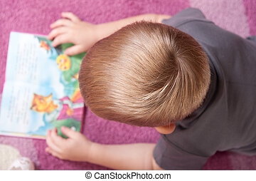 Cute boy is reading book - Cute boy aged 3 is lying on the...