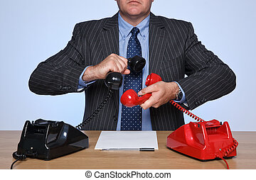 Businessman sat at desk with two telephones.