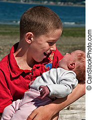 Big Brother Holding Baby Sister - This shows a loving big...