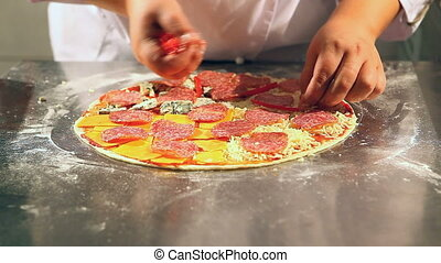 pizza - chef puts salami in to the pizza